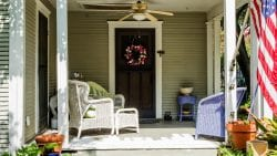 House hunting — front porch of house with wicker furniture on a sunny day