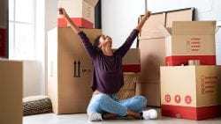 Young woman celebrates her first home purchase surrounded by moving boxes